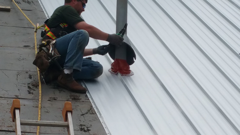 Worker Installs an EPDM Heat-Resistant Boot around a Gas Water Heater Exhaust Pipe on a Standing Seam Metal Roof