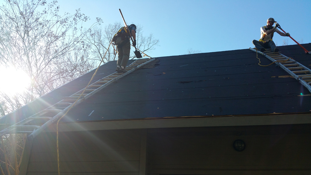 Removing shingles off a steep-slope roof. Owner Brad Caldwell pictured on left.